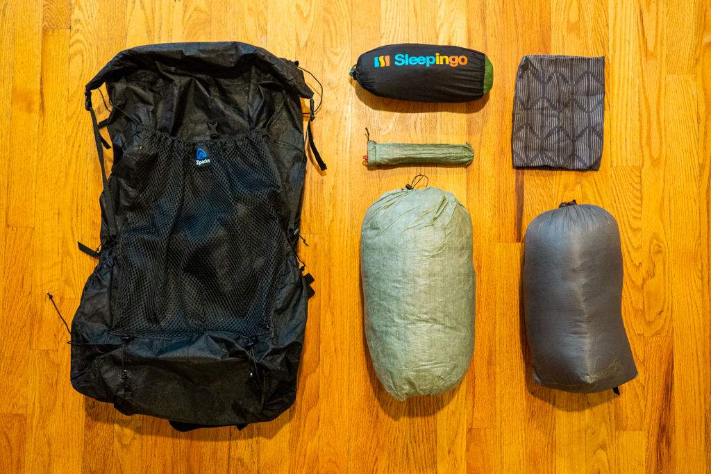 Backpack, tent, stakes, sleeping bag, sleeping pad, and pillow case laid out across a wood floor