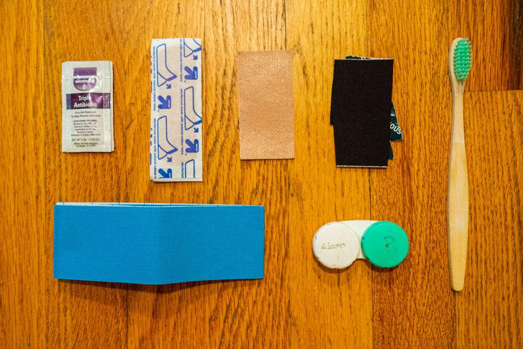 Antiseptic, Band-Aids, blister pads, Tenacious Taps, Leukotape, contact case, and a toothbrush laid out across a wood floor