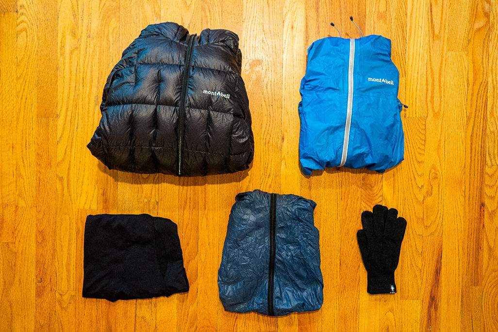 Down jacket, rain jacket, thermal top, wind breaker, and gloves laid out across a wood floor