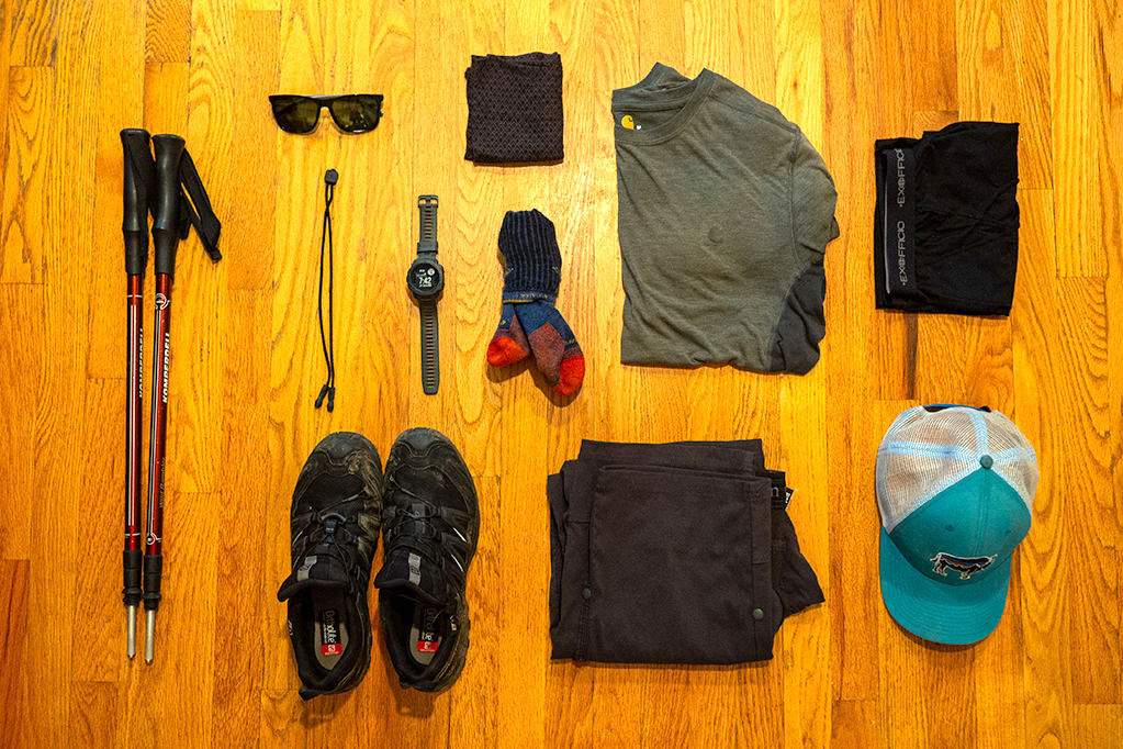 Ultralight backpacking gear: trekking poles, sunglasses, watch, shoes, Buff, socks, pants, shirt, boxer briefs, and hat laid across a wood floor