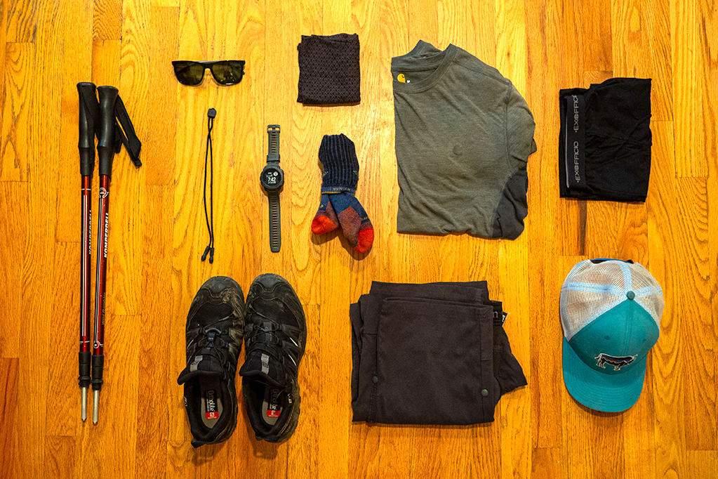 Ultralight backpacking gear: trekking poles, sunglasses, watch, shoes, Buff, socks, pants, shirt, boxer briefs, and hat laid across a wood floor