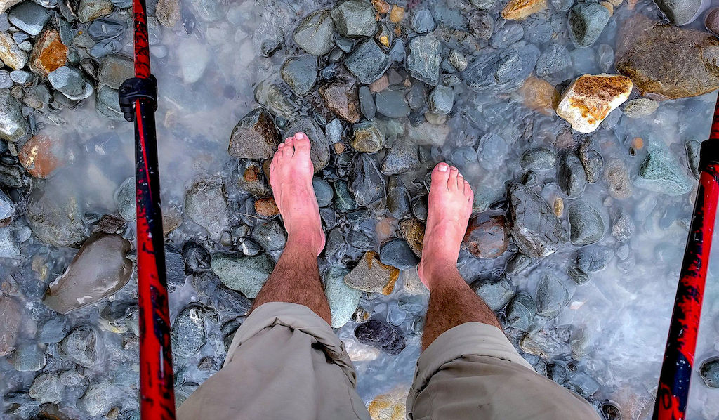 Feet and trekking poles standing in blue-grey glacial water