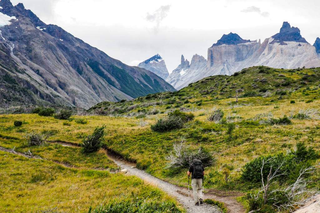 A hiker walks down a trail towards a Torres del Paine mountain range in the distance