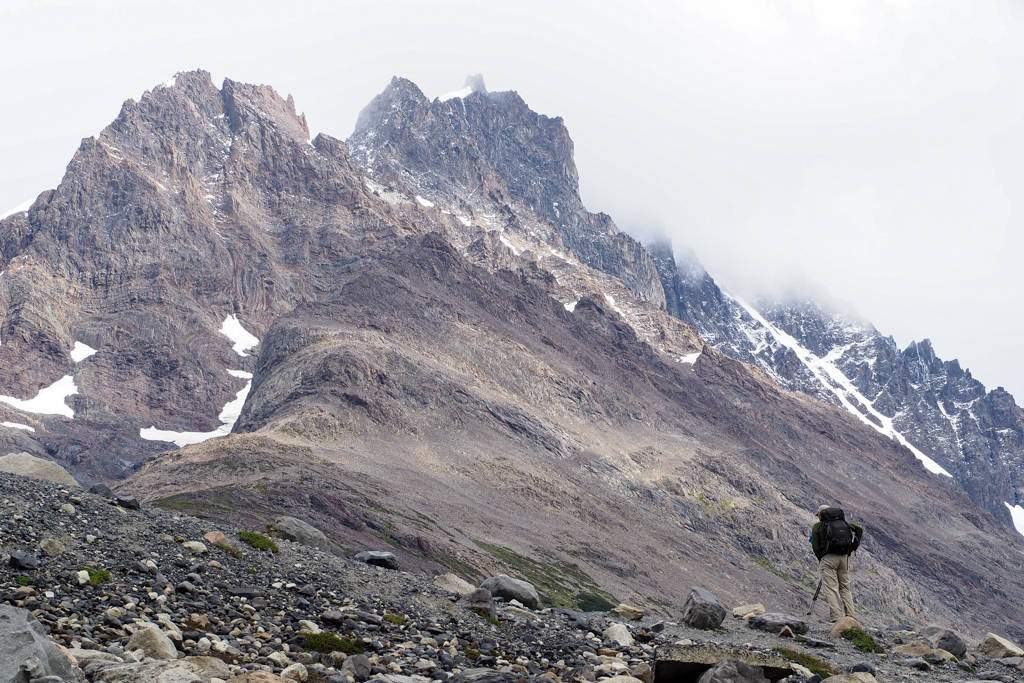 An ultralight backpacker gazes at a foggy mountain range in the distance