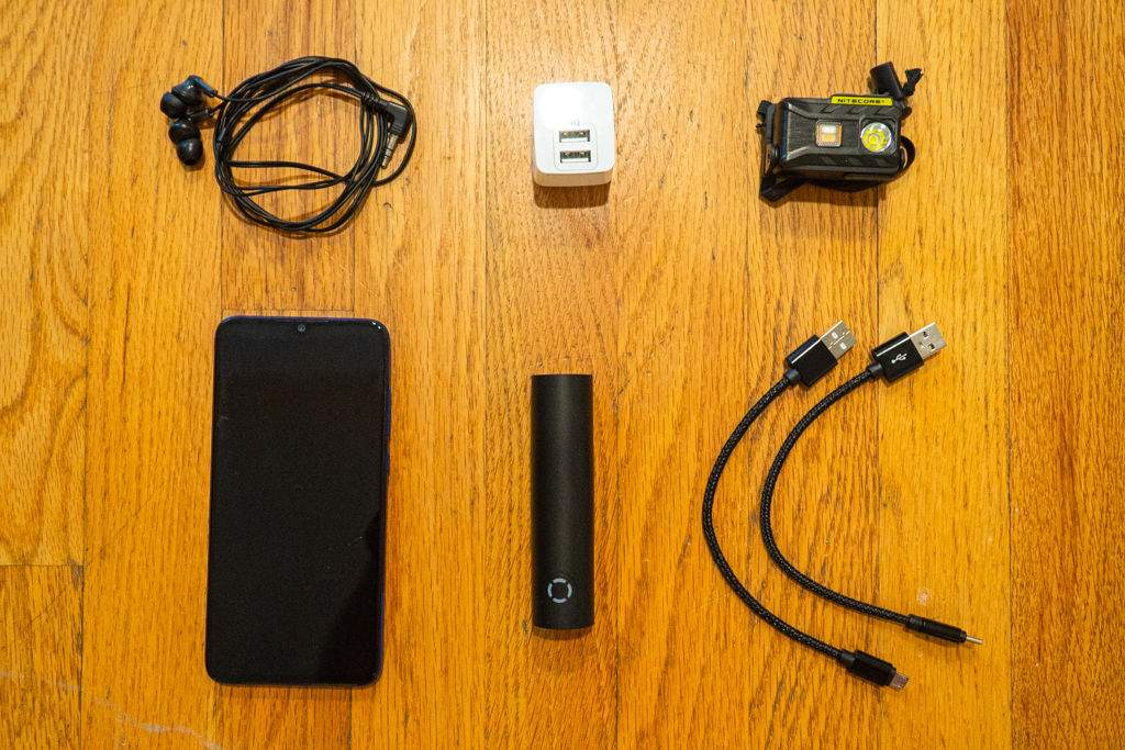 Headphones, phone, wall charger, power bank, USB cords, and a headlamp laid out across a wood floor