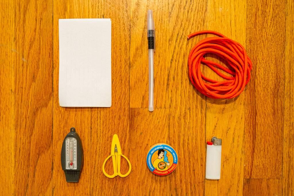 Paper, pen, paracord, thermometer, scissors, towel, and mini lighter laid out across a wood floor