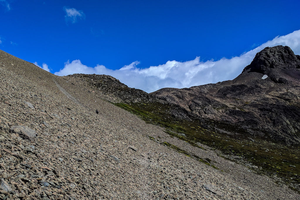 A large field of rocks leading up to Paso del Viento with a blue sky backdrop