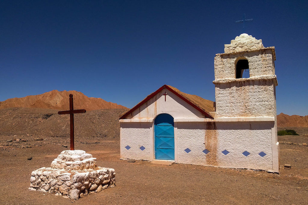 A small white and blue chapel with a cross out front sitting on red desert dirt with blue skies