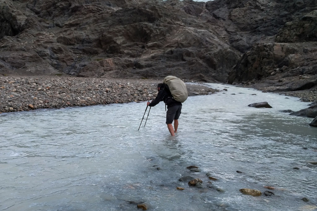 A hiker crossing the blue-grey Tunel River with his trekking poles and a large backpack