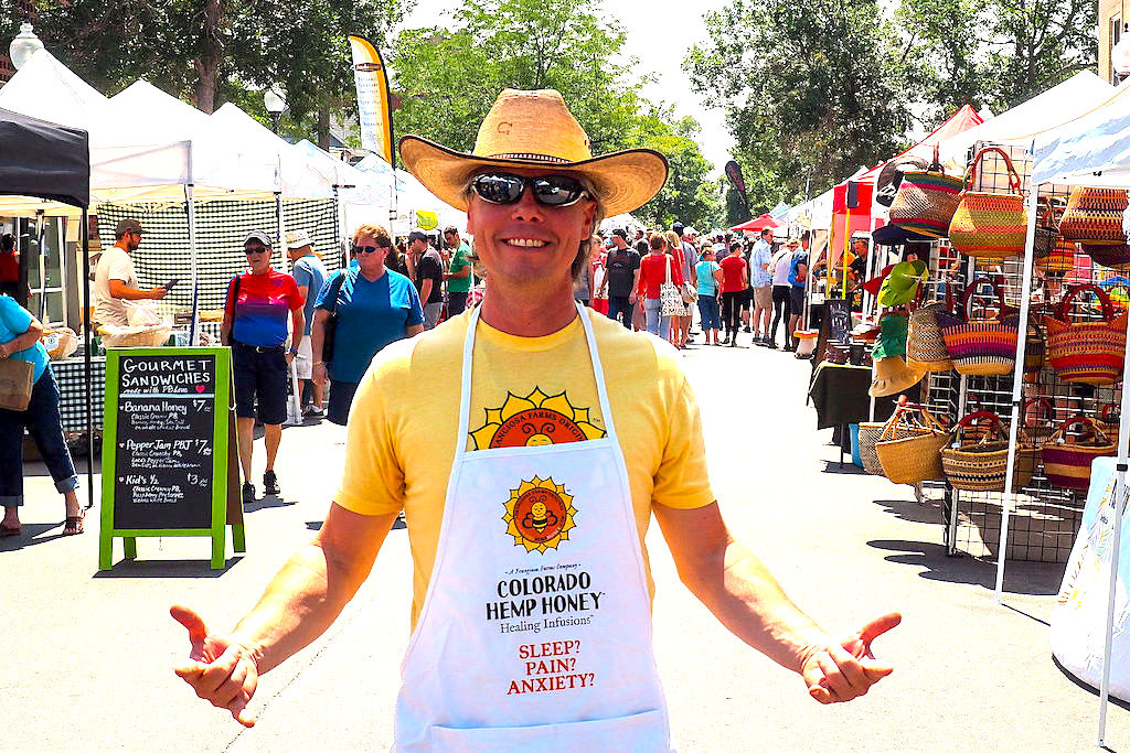 A budget beekeeper wearing a cowboy hat stands on front of a farmers market in Denver