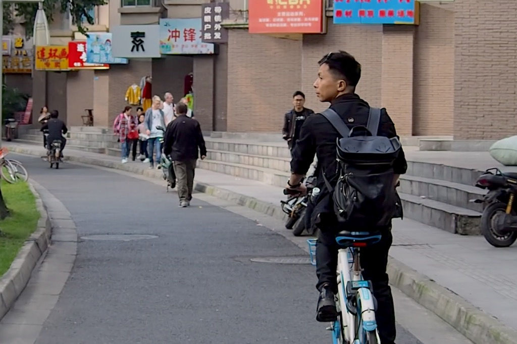 A man riding his bike down the street in Chengdu, China
