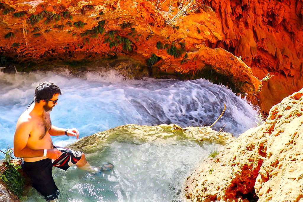 A man who spent his travel savings to see the world sits atop Mooney Falls in Havasupai Falls, Arizona
