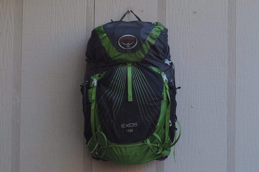 Osprey Exos 48 backpack against a green house