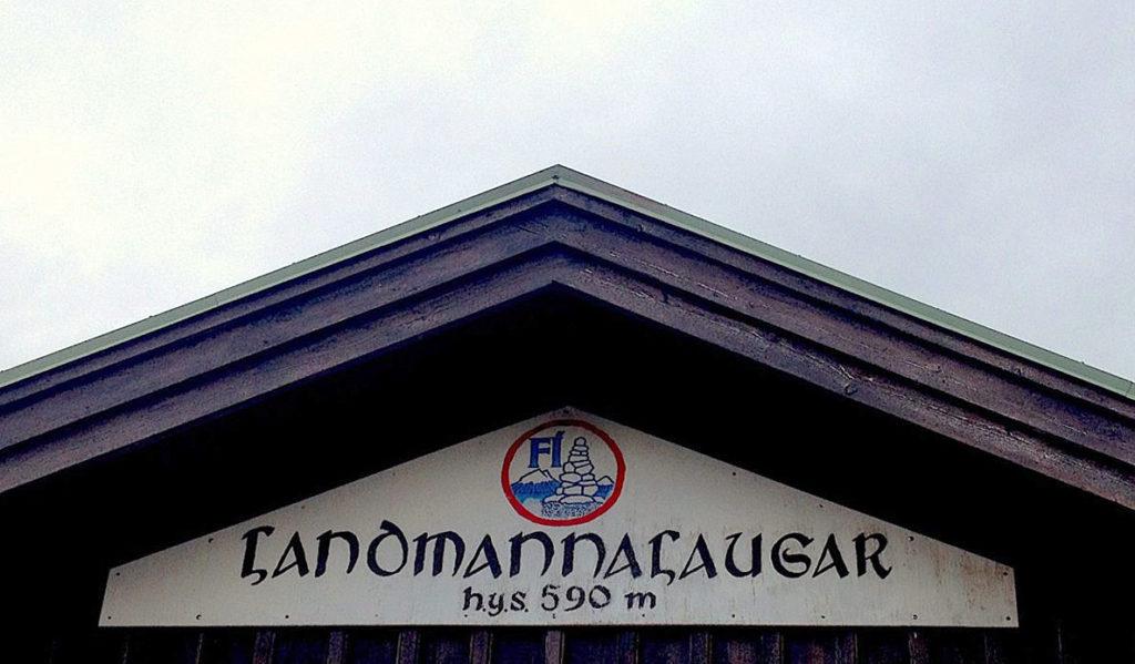 """A sign affixed to a hut reading """"Landmannalaugar - 590m"""""""
