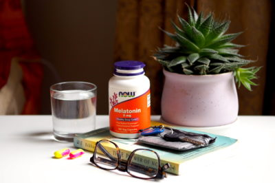 Water, earplugs, glasses, melatonin, and a plant on a bedside table in a hostel to help sleeping