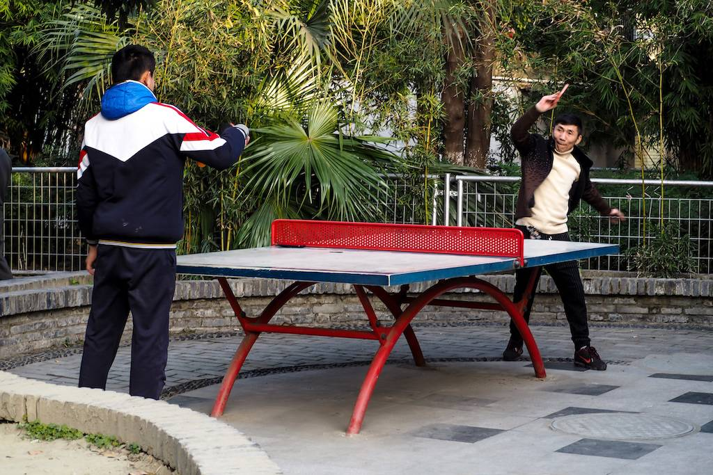 Two men passionately playing outdoor ping pong