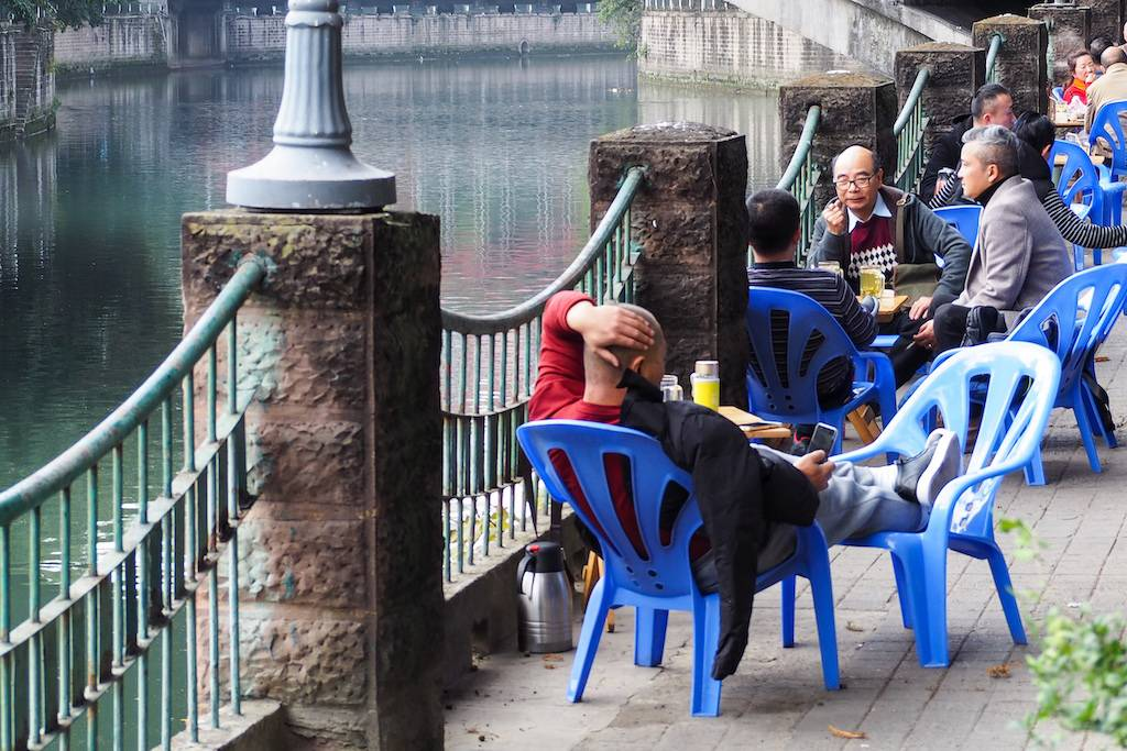 Tables full of happy people sipping tea by the Jinjian River in Chengdu, China