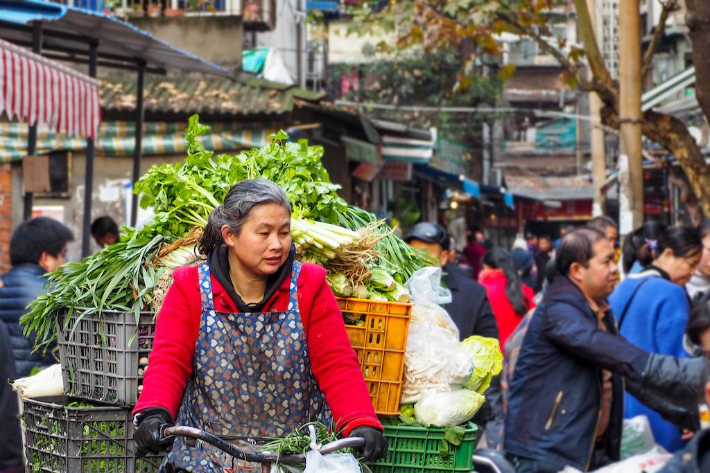 Woman riding a bike in a crowded alley market in Chengdu, China