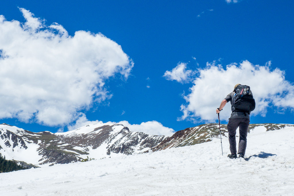 A backpacker trudges over snow towards mountains and clouds in the distance