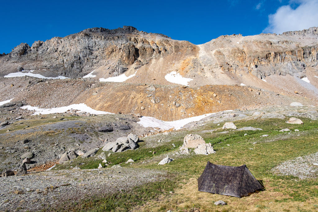 An ultralight camo tent, essential backpacking gear, in front of a Colorado mountain range