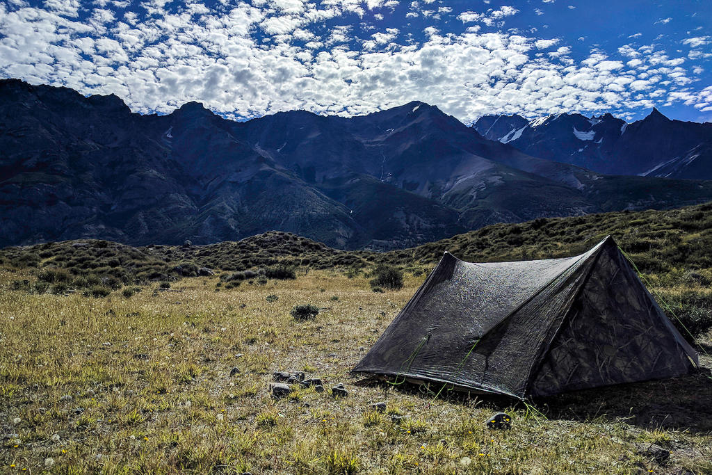 A Zpacks Triplex tent pitched in front of a mountain range on the Huemul Circuit in El Chalten, Argentina
