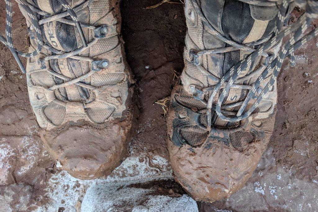 Above view of muddy boots on a hiking trail