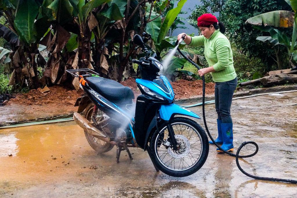 A woman spray washing a muddy blue motorbike