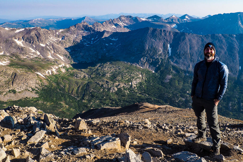A man facing the camera standing on top of Mount Lincoln in Colorado
