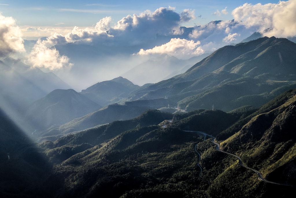 Sunbeams shining through clouds over lush green Vietnam mountains while motorbiking through
