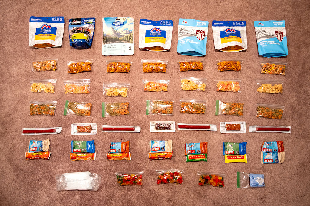 Seven days of backpacking food, meal planned and laid out in rows across a carpet