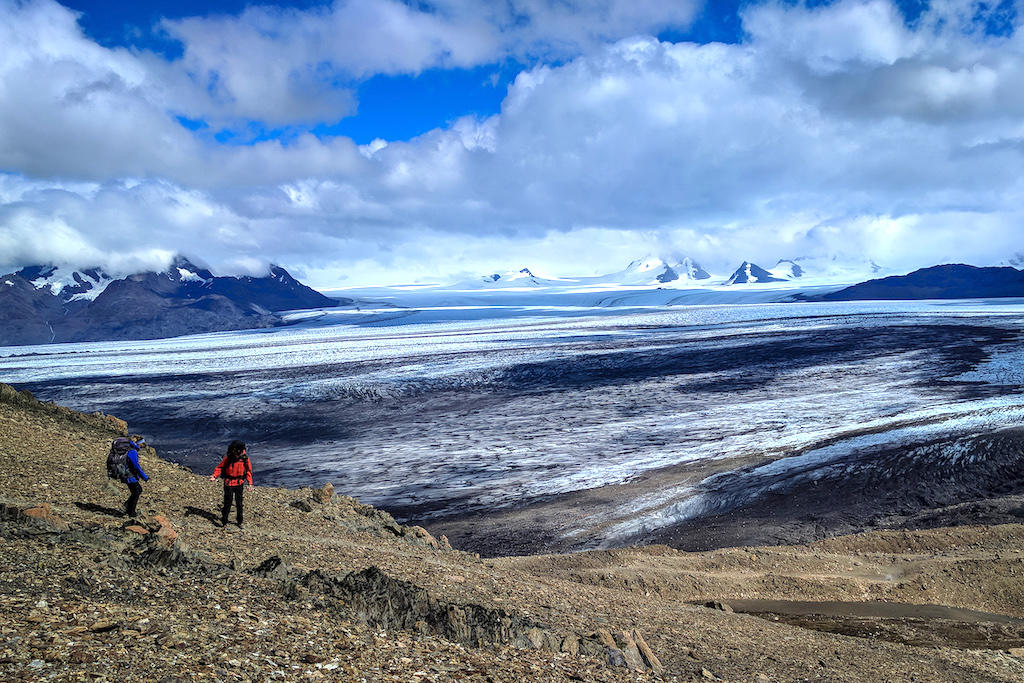 Hikers look out over a glacier field