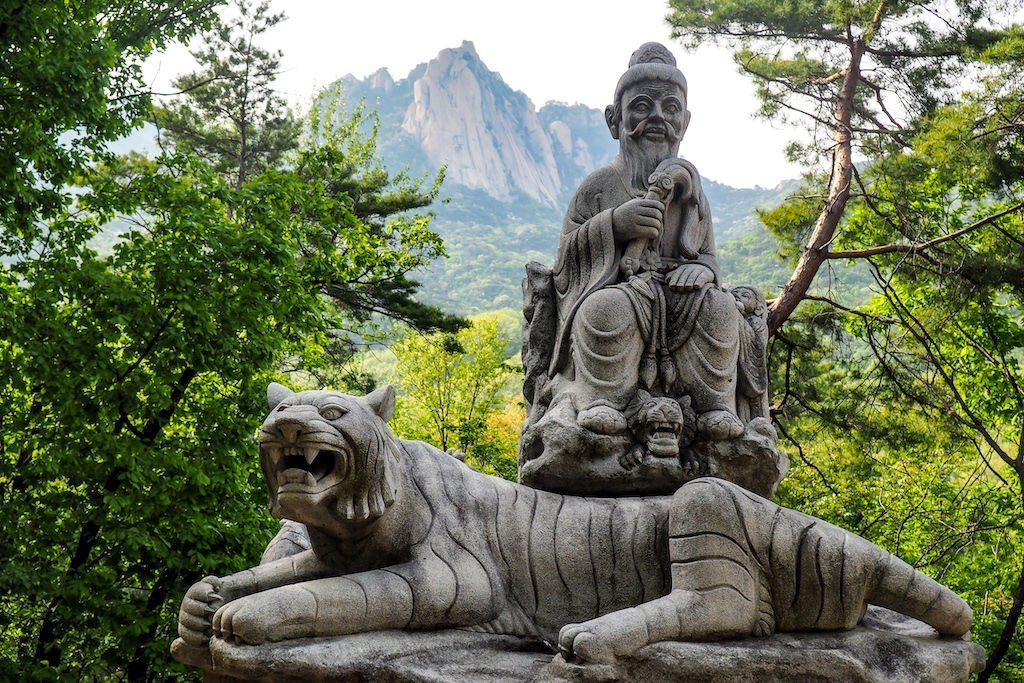 Statue of man and tiger with a backdrop of Dobongsan Mountain in Bukhansan National Park near Seoul
