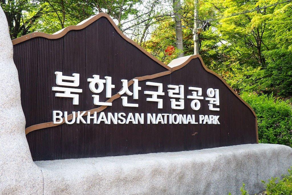 "A white sign against a black backdrop that says ""BUKHANSAN NATIONAL PARK"""