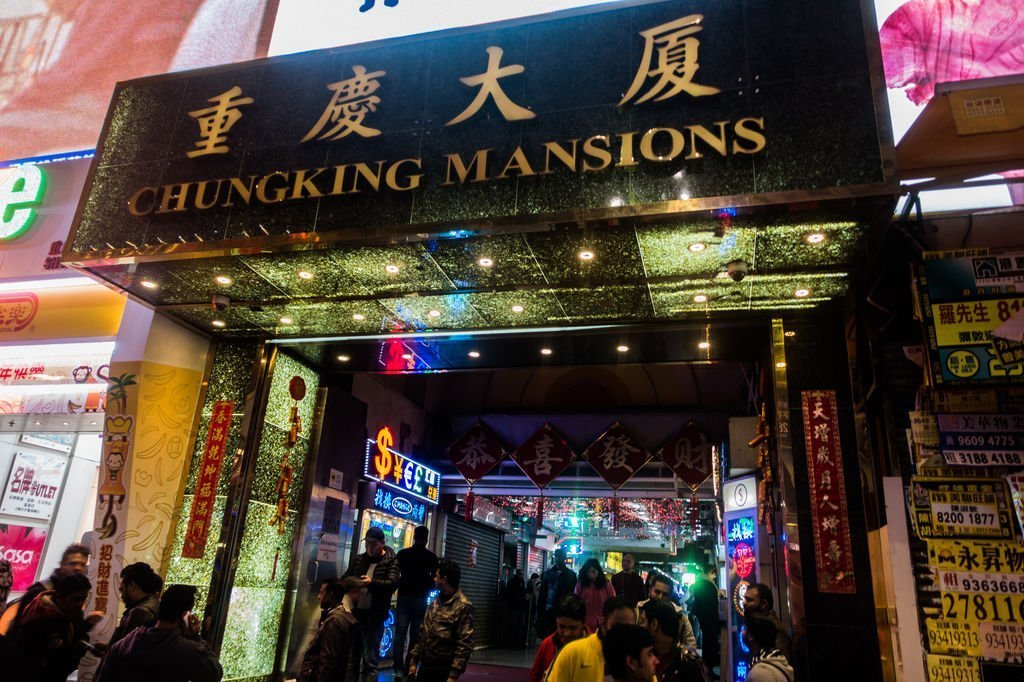 "View of the front of a high rise with ""Chungking Mansions"" over the front entrance"