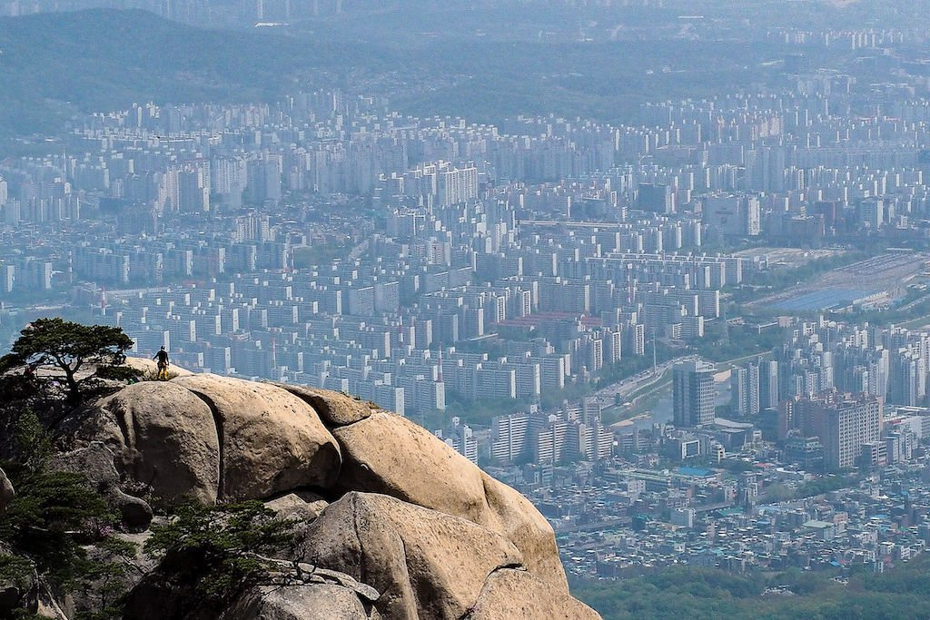 A climber stands atop Gwanaksan Mountain and looks over Seoul, South Korea
