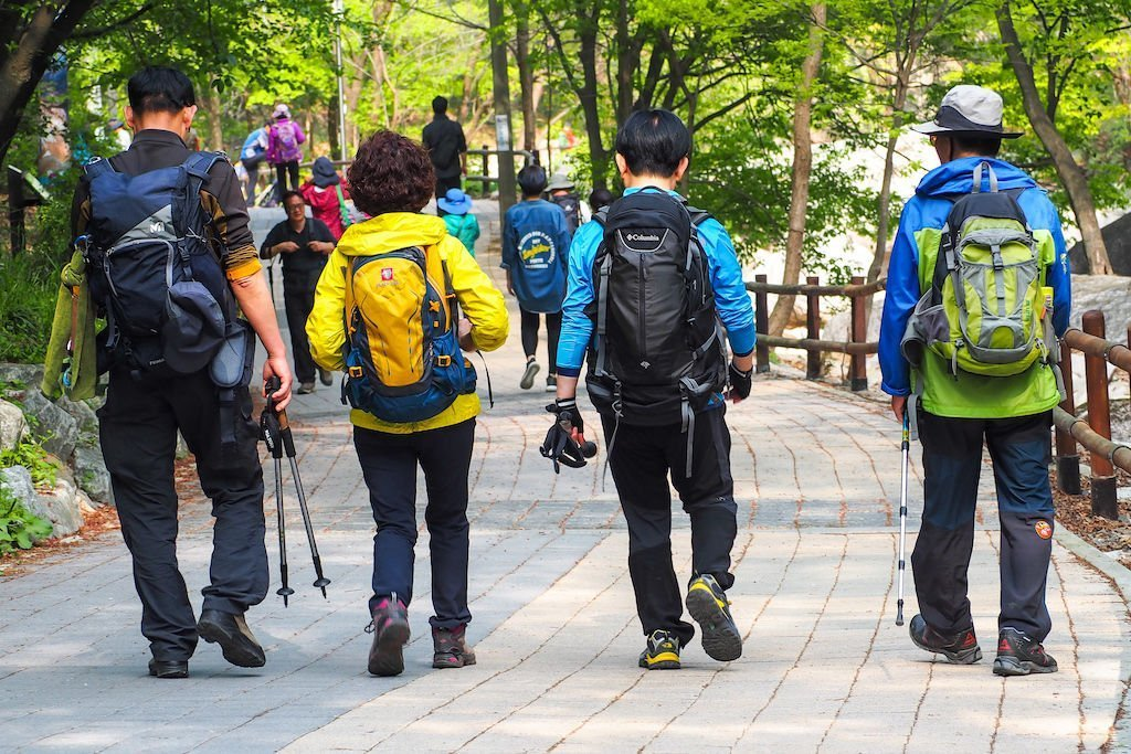 Four people decked out in colorful hiking gear walking down a paved path towards Dobongsan Mountain