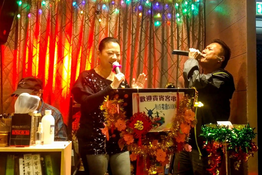 A man and a woman passionately singing karaoke in a dimly lit bar