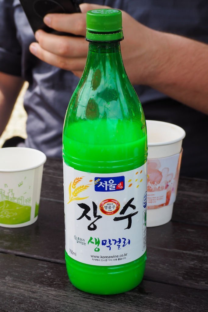A green bottle of makgeolli, a cloudy, sparkling Korean alcohol