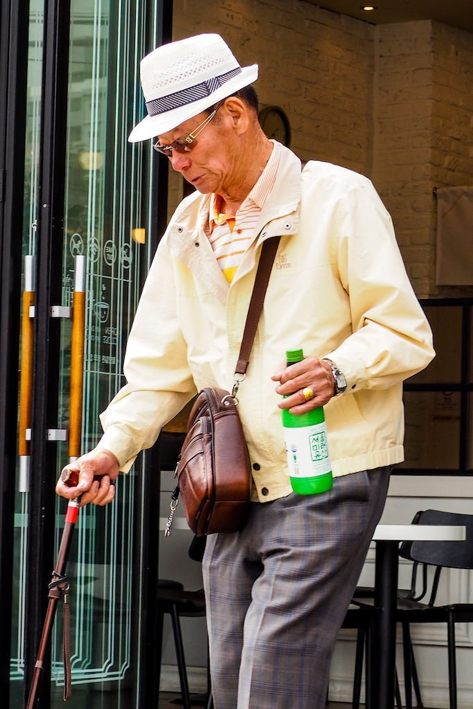 A man with a white fedora and a walking cane walking with a green plastic bottle of makgeolli in his hand