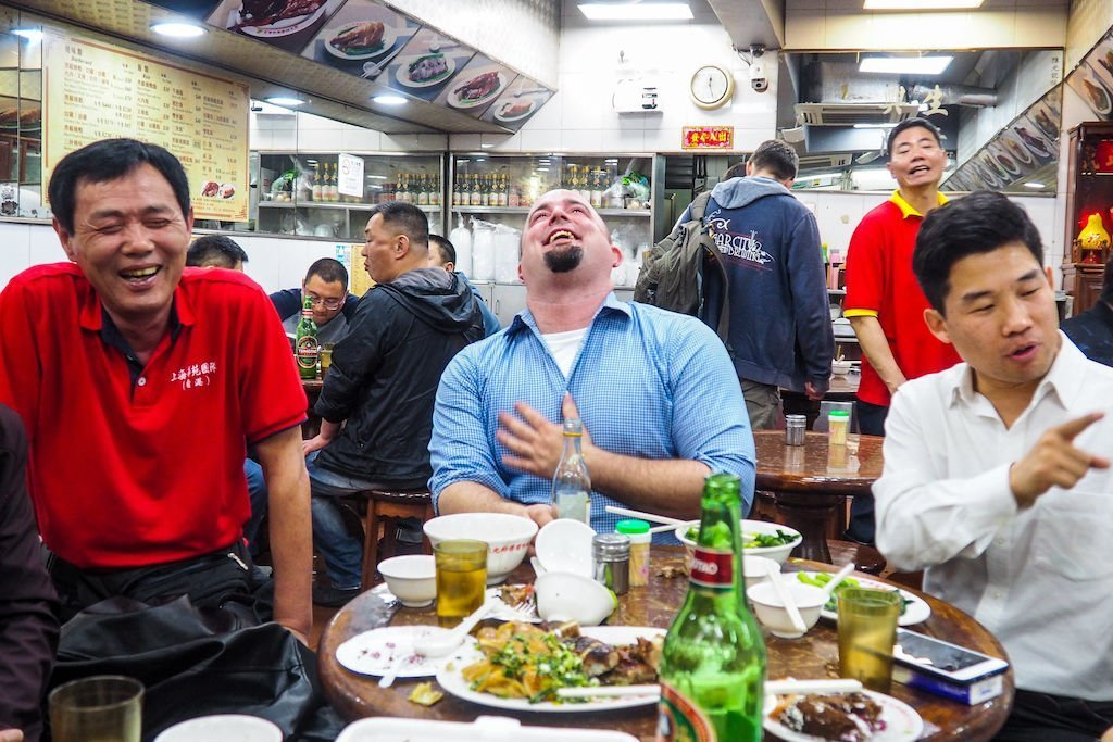 Three men in a restaurant laughing at a messy table