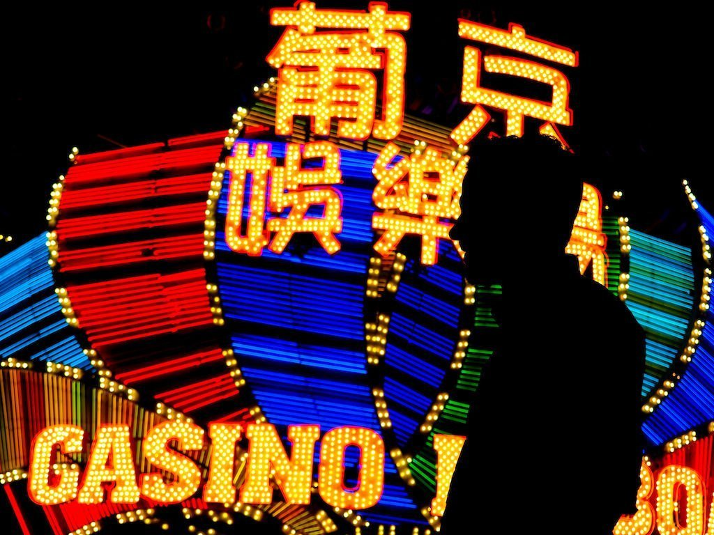 Side profile silhouette of a man standing in front of a brightly lit casino in Macau