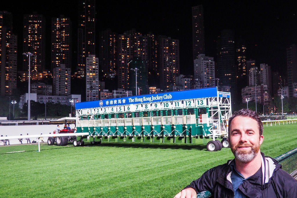 Man standing in front of the racetrack at Happy Valley Racecourse in Hong Kong