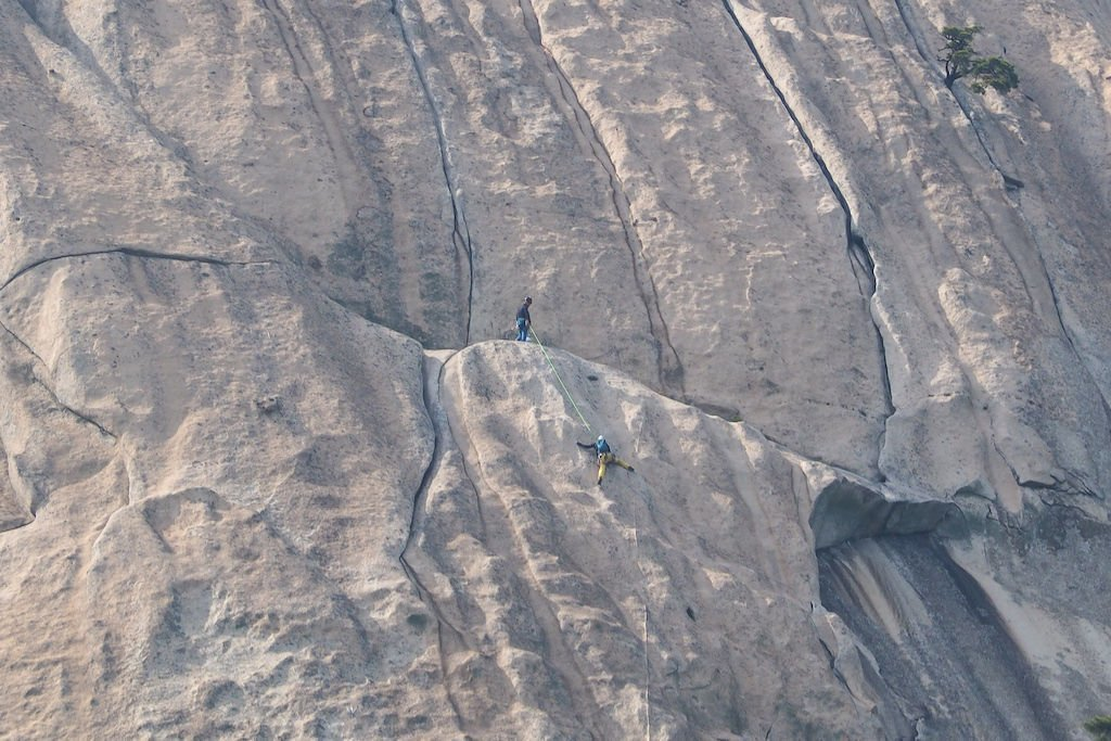 Two mountain climbers ascending a sheer face of rock