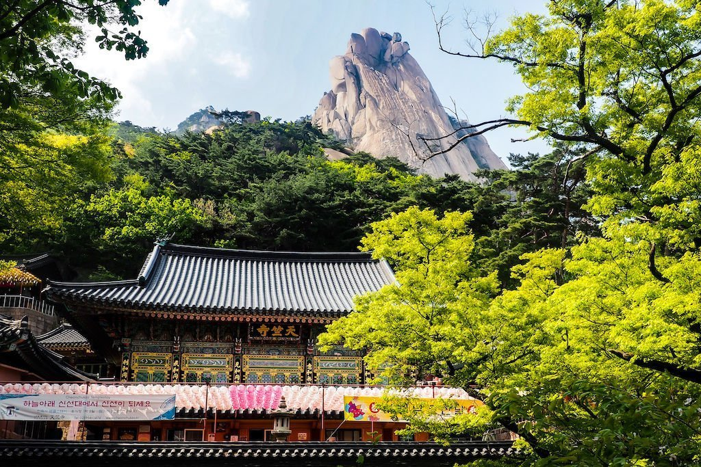 A temple, a tree with yellow leaves, and a jagged mountain peak against blue skies