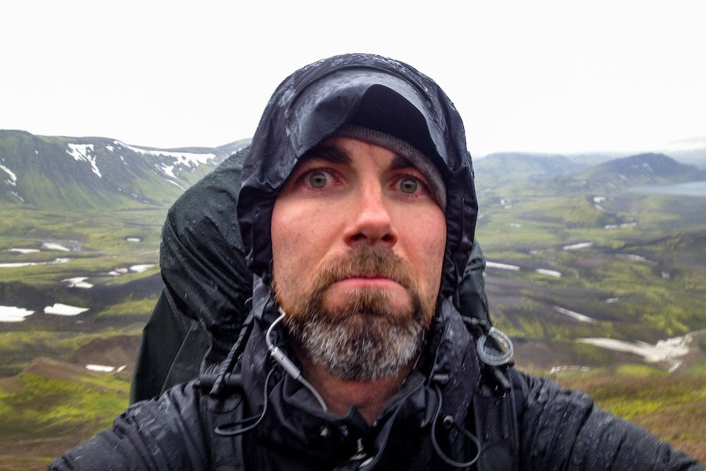 "A weary hiker with a ""travel sucks"" expression on his face, soaked in rain during a trek in Iceland"