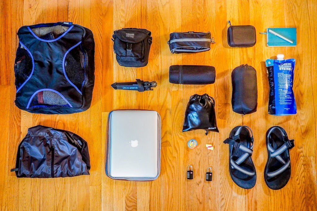 Carry on packing list gear laid out across a wood floor