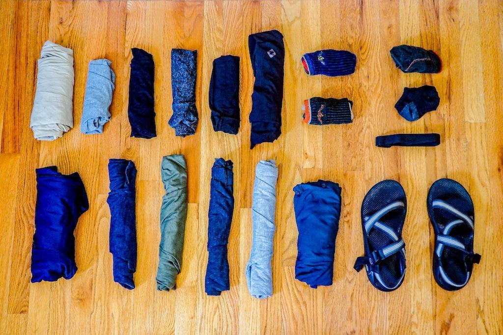 Travel clothing spread across floor for reference as part of carry-on only packing list