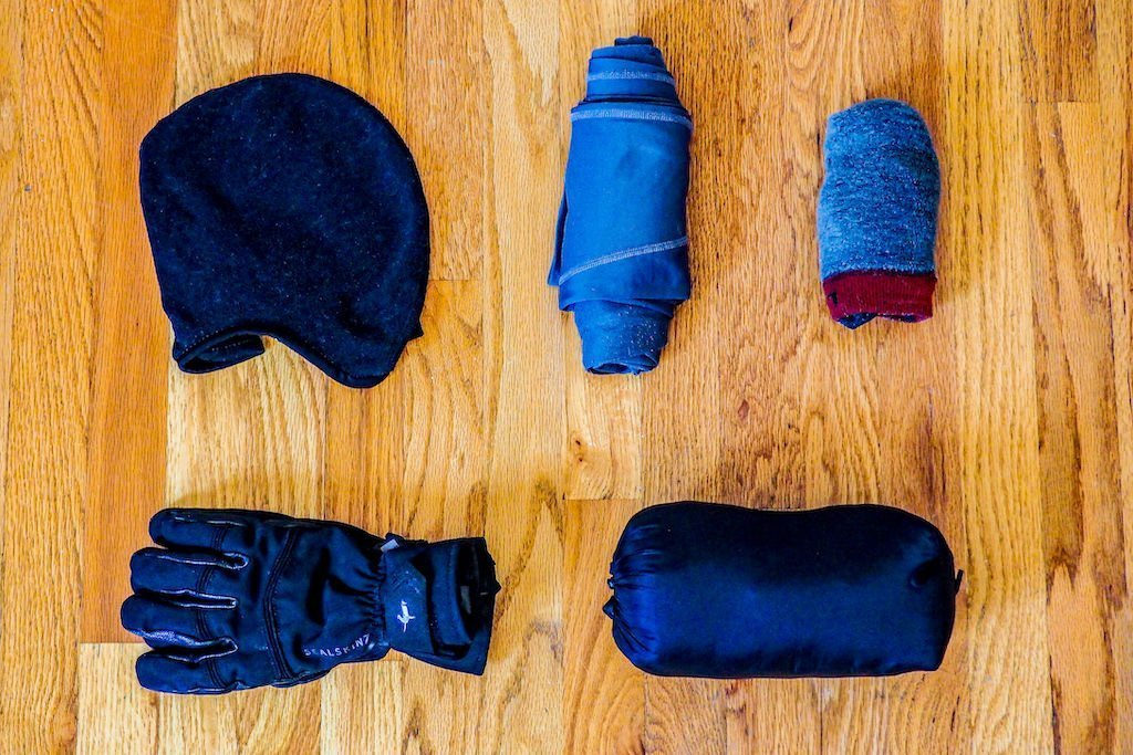 Gloves, hat, long underwear, socks, and down jacket on hardwood floor