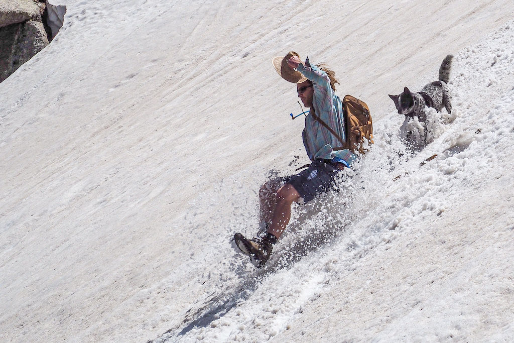 A man in mid air glissading down a snowbank as his dog follows closely behind on the Chicago Lakes hike in Colorado