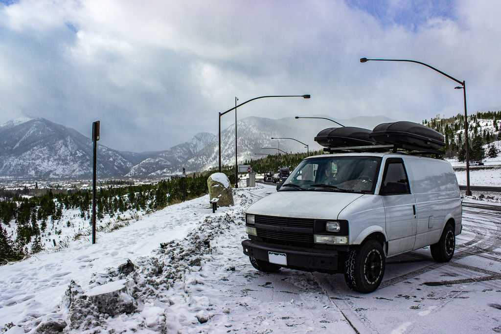 A white camper van pulled into a snowy parking spot with mountains and light posts in the background